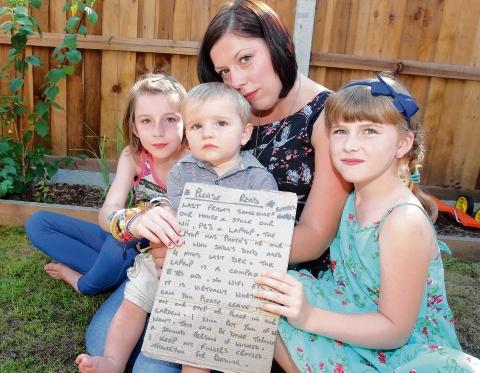 How could you? Murron ten, Hamish, one, and Iona, seven, with mum Sam Cozier and their sign to the thief