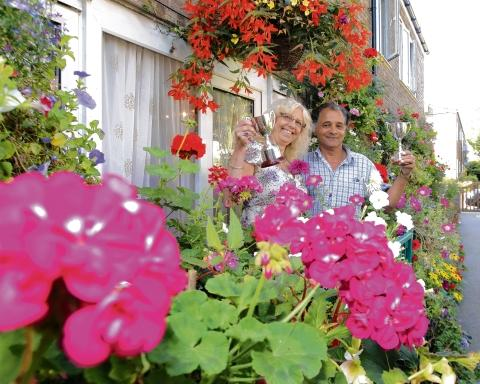 All smiles –  Leroy Fox and Cheryl Gainty  in their beautiful and colourful garden at Charles Smith House Ladbrook Drive, Colchester, with their  Colchester in Bloom trophies