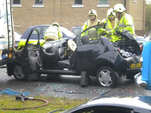 Firefighters cut the roof of a Ford Ka after the driver was trapped by her injuries.
