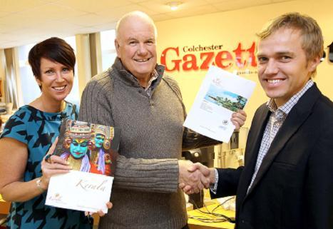 Malcolm Smith (centre) gets his prize from Nigel Barton , managing director of Kerala Travel, and Tanya Rees, the Gazette's promotions manager