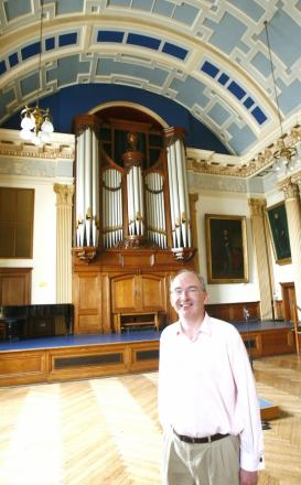 Cllr Nigel Chapman, chairman of Friends of the Moot Hall Organ, in front of the organ.