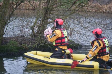 Firefighters paddle out to the trapped moorhen