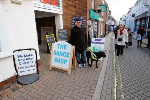Blind people have had problems with A-boards in Colchester. Phil Lee negotiates A-boards in Sir Issac Walk.