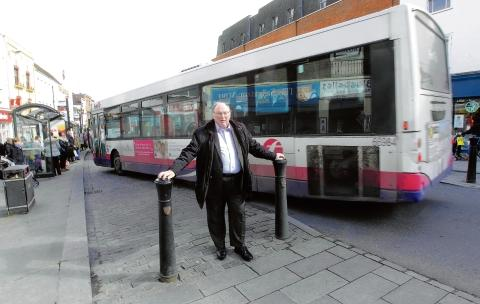 Cllr Terry Sutton by High Street bollards which stop buses pulling into stops effectively.