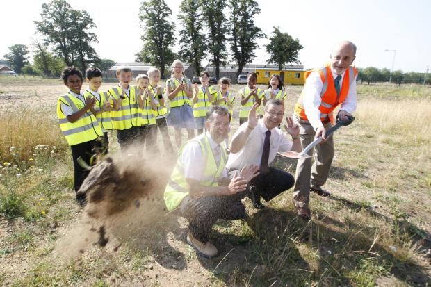 Essex County Standard: St John's Green pupils watch (from left) county councillor Don Parker, headteacher  Simon Billings and county councillor Ray Gooding cutting the first sod.