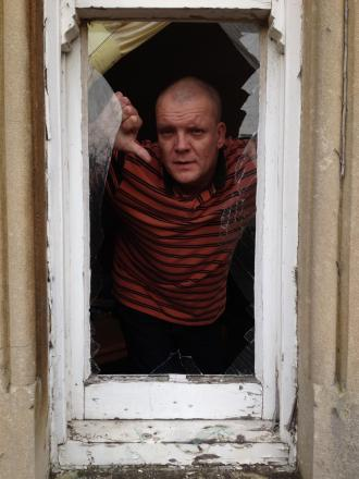 Mark Wild inside his flat where the window was smashed