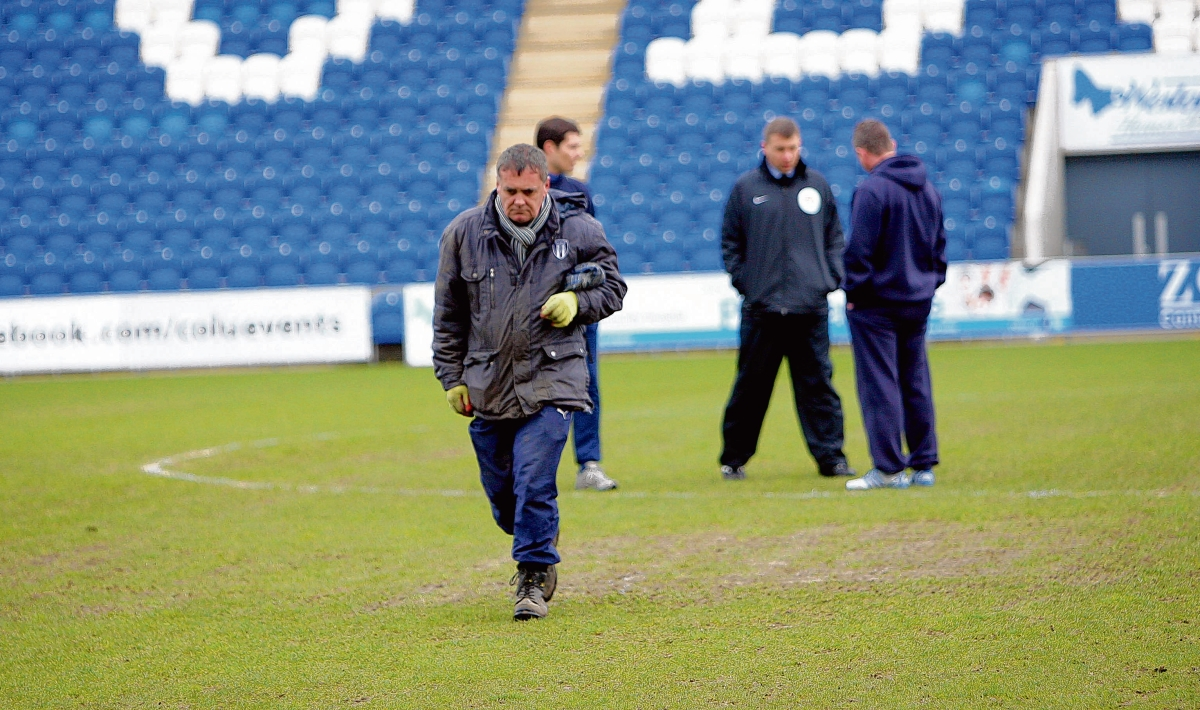 Frustration - U's head groundsman David Blacknall walks off the pitch following the postponement of Colchester's game with Shrewsbury yesterday. Picture: ADRIAN RUSHTON