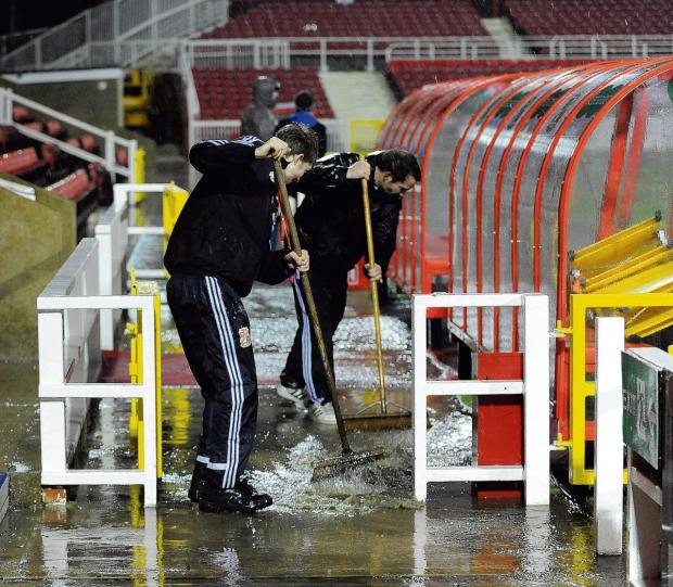 Essex County Standard: Sweepers - Swindon Town groundstaff remove some of the water prior to the U's 0-0 draw with Swindon Town, last Friday. Picture: WARREN PAGE