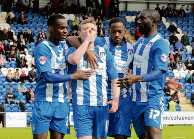 Relief - Colchester United's players are all smiles following Freddie Sears' goal against Brentford. Picture: NIGEL BROWN (CO90950-37)